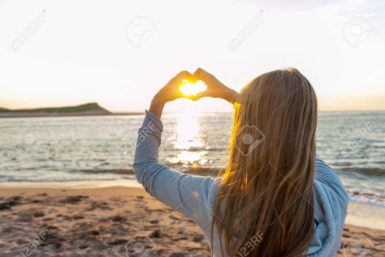 Jovencita Rubia Con Las Manos En Forma De Corazón Enmarcado Sol Al ...