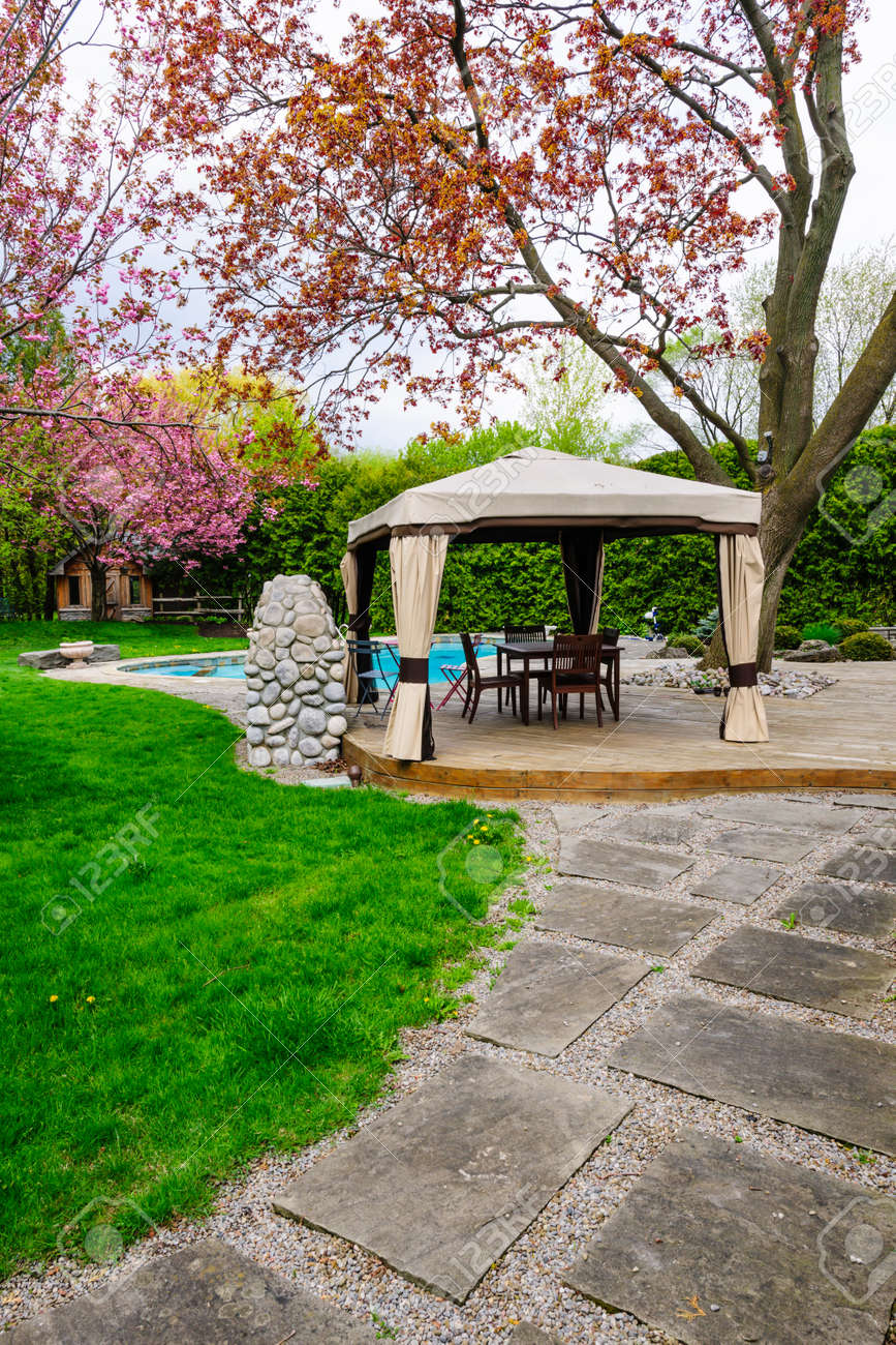 residential backyard with gazebo deck stone patio and swimming