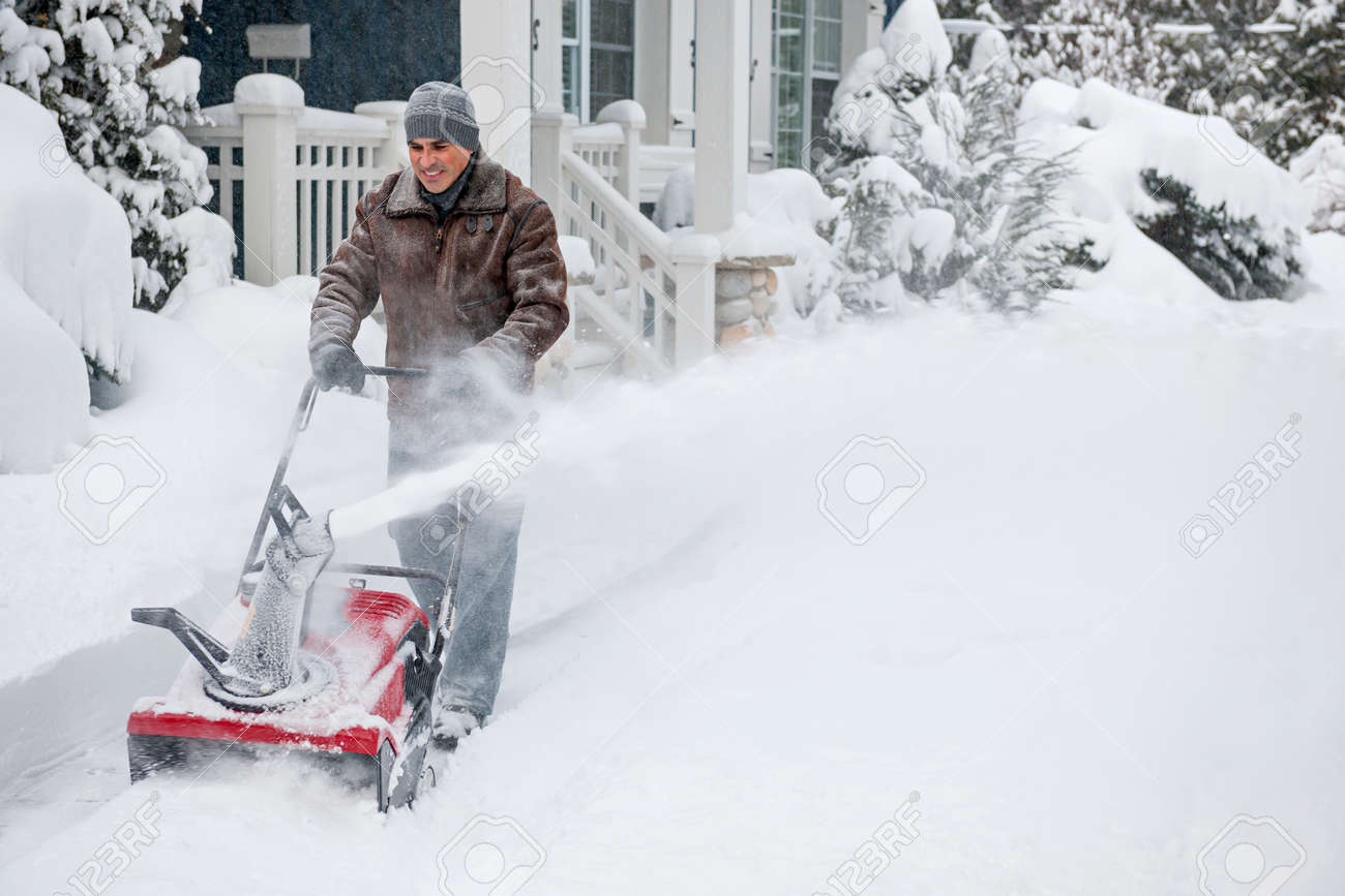 Man using snowblower to clear deep snow on driveway near residential house after heavy snowfall. Stock Photo - 25672703