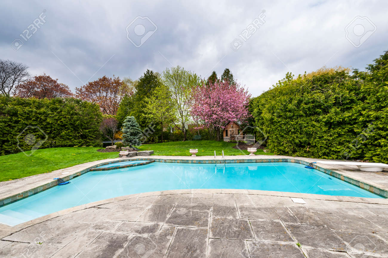 Backyard of residential house in spring with large pool and paved patio - 27583990