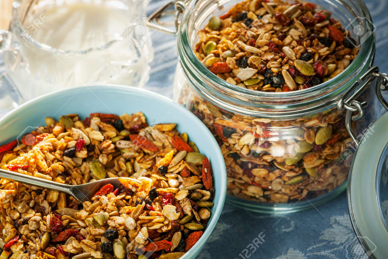 Serving of homemade granola in blue bowl and milk or yogurt on table with linens Stock Photo - 27340410