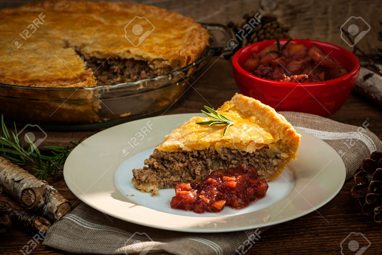Slice of traditional pork meat pie Tourtiere with apple and cranberry chutney from Quebec, Canada. - 27340416