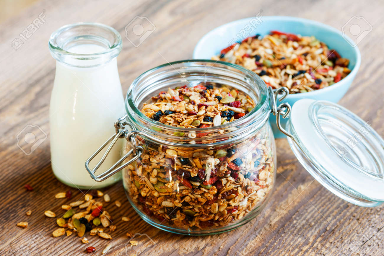 Homemade granola in open glass jar and milk or yogurt  on rustic wooden background Stock Photo - 27768056