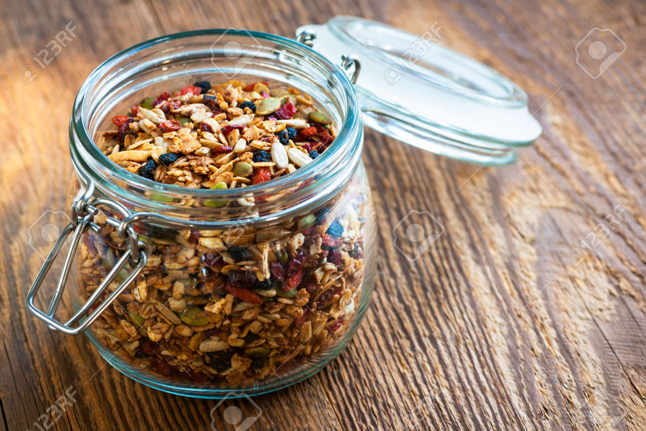 Homemade granola in open glass jar on rustic wooden background - 27768053