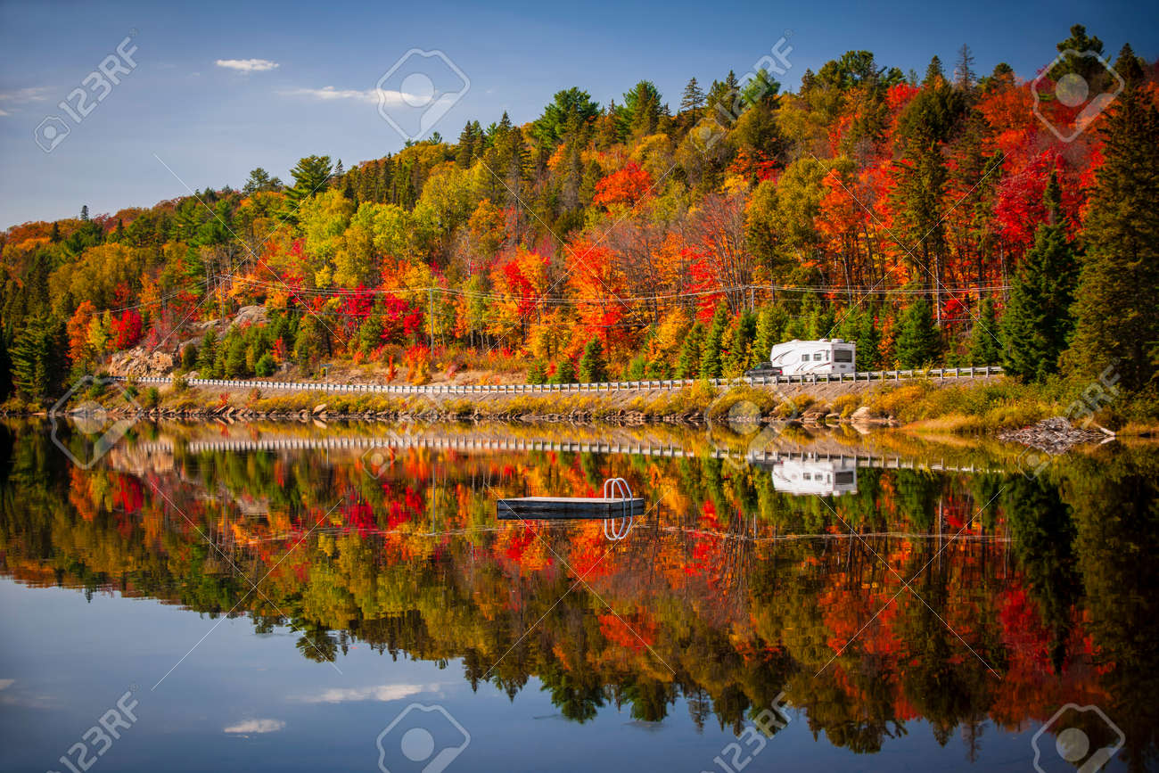 Fall forest with colorful autumn leaves and highway 60 reflecting in Lake of Two Rivers.  Algonquin Park, Ontario, Canada. Stock Photo - 28287600