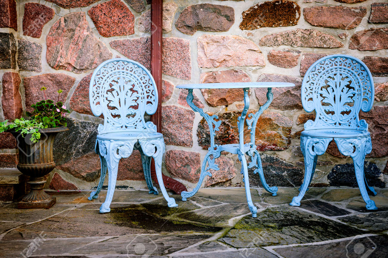 Blue painted metal outdoor furniture on stone patio - 28917359