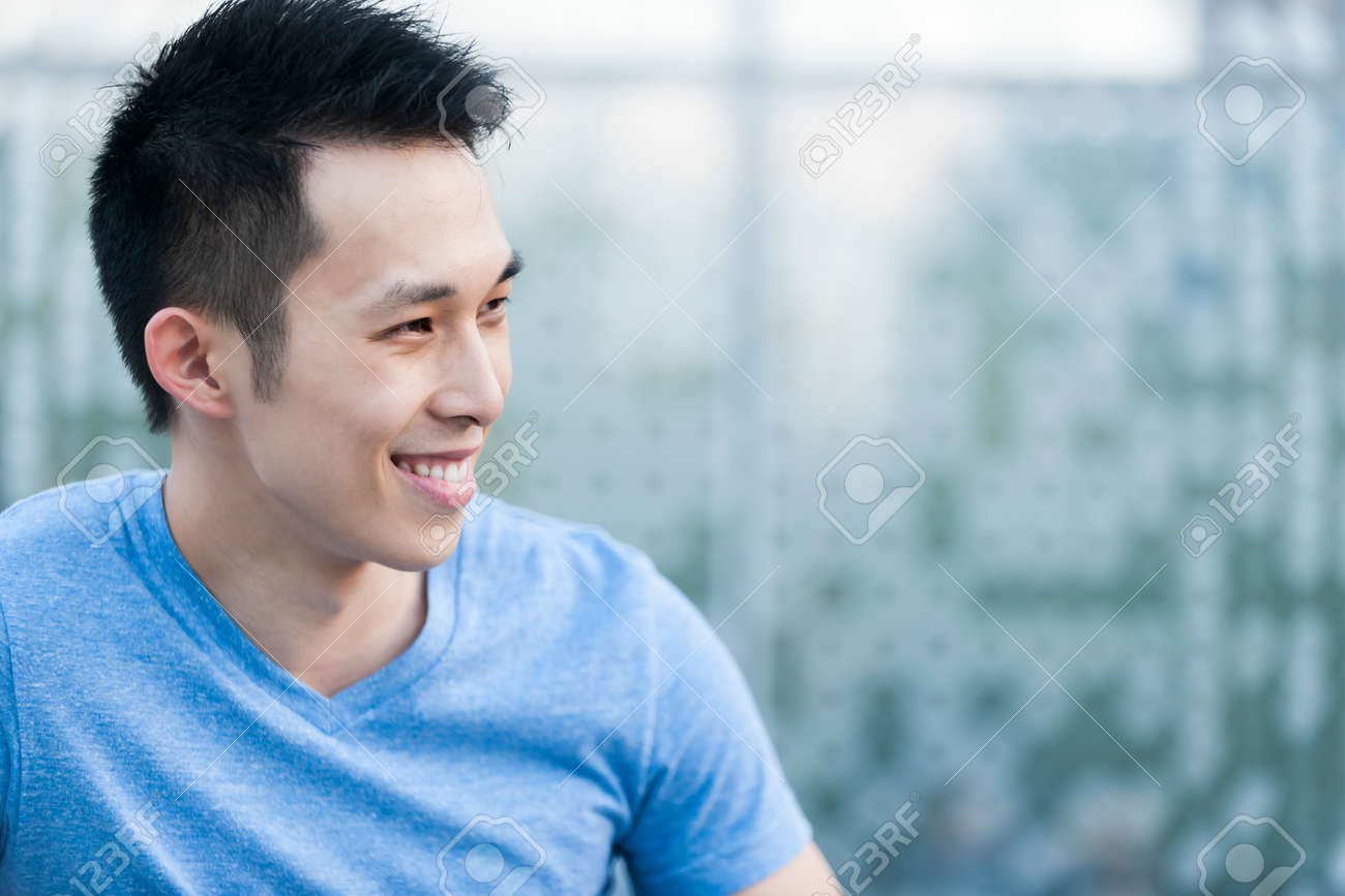 Portrait of confident young asian man in profile smiling on blue background with copy space - 31947592