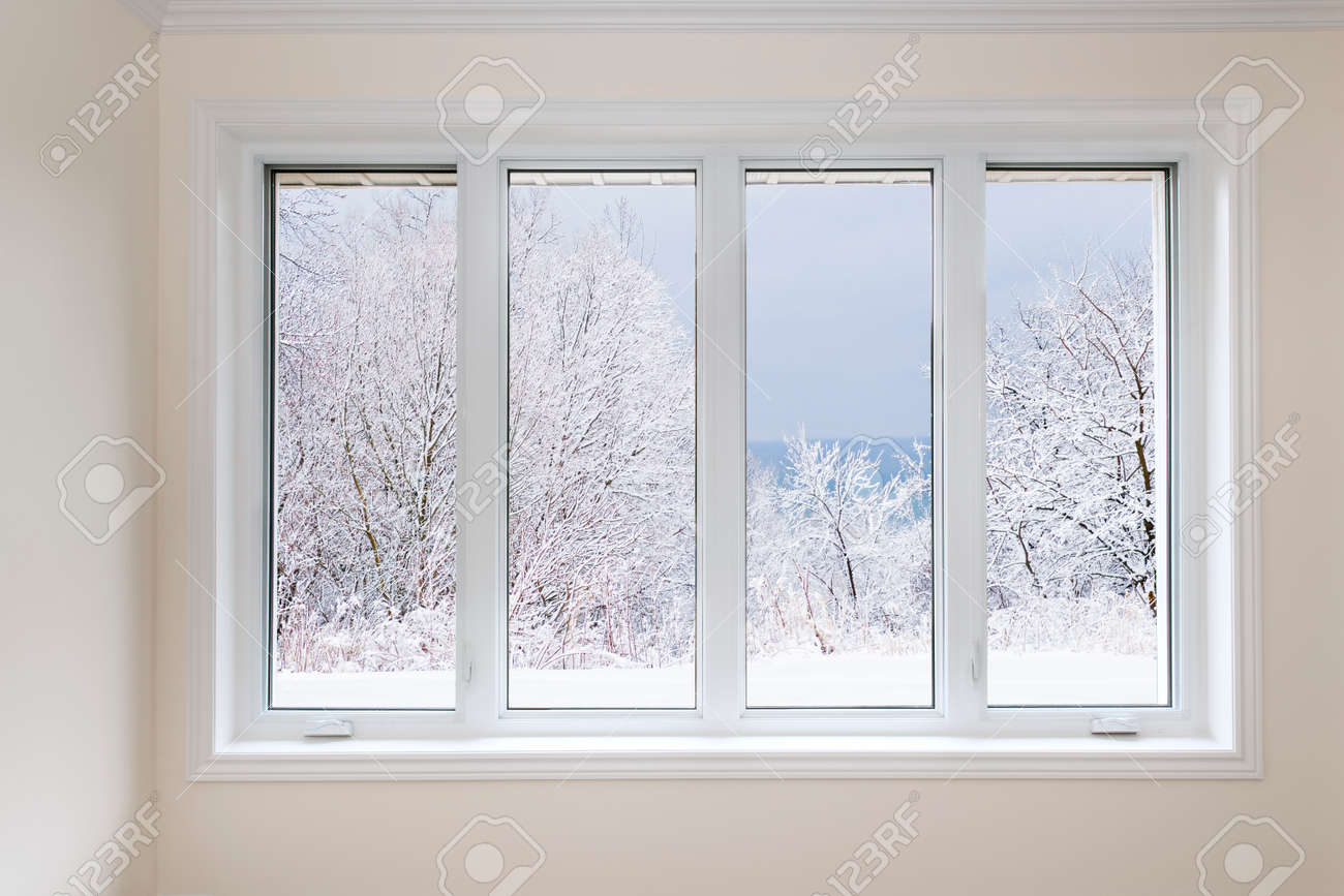 Large four pane window looking on snow covered trees in winter - 33879228
