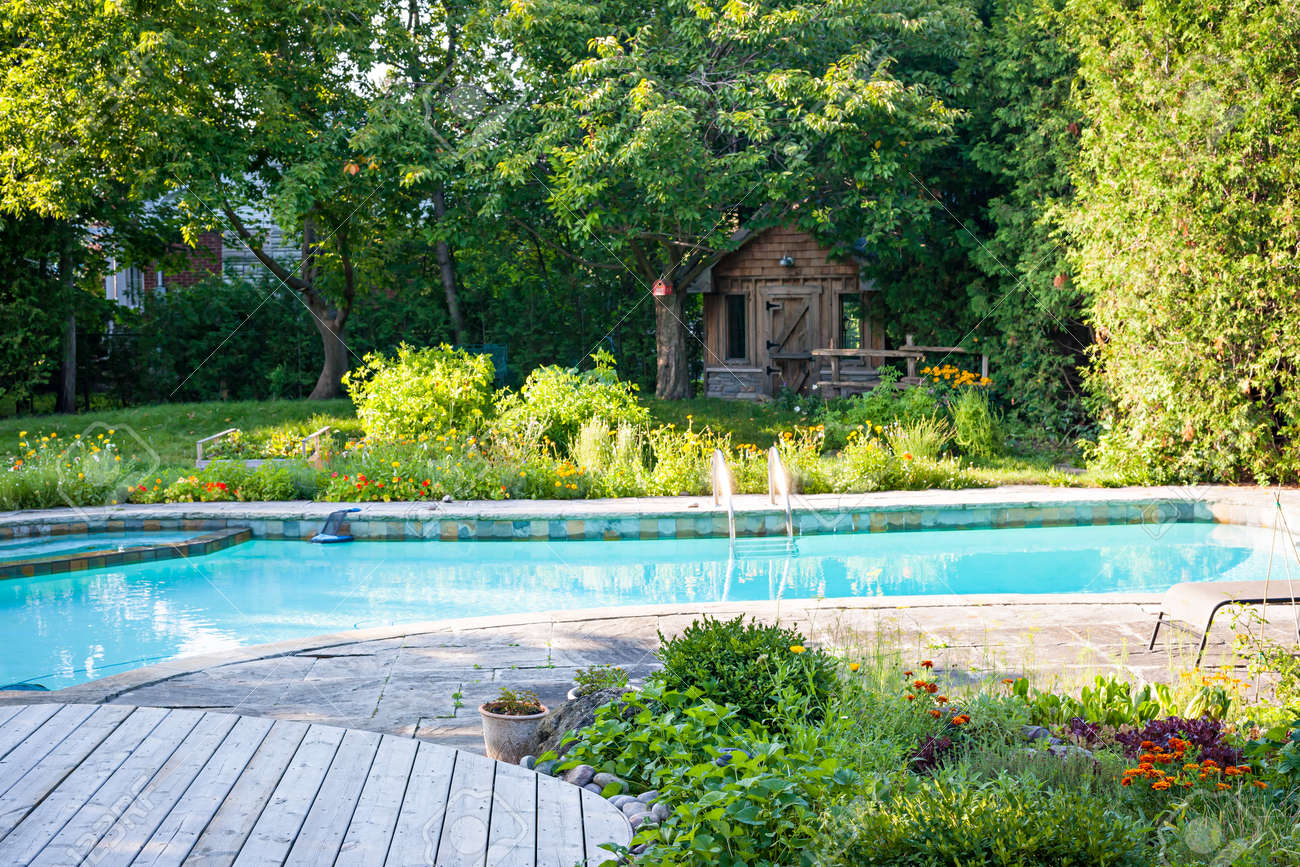 Backyard with garden, shed, outdoor inground residential swimming pool, curved wooden deck and stone patio - 34154490