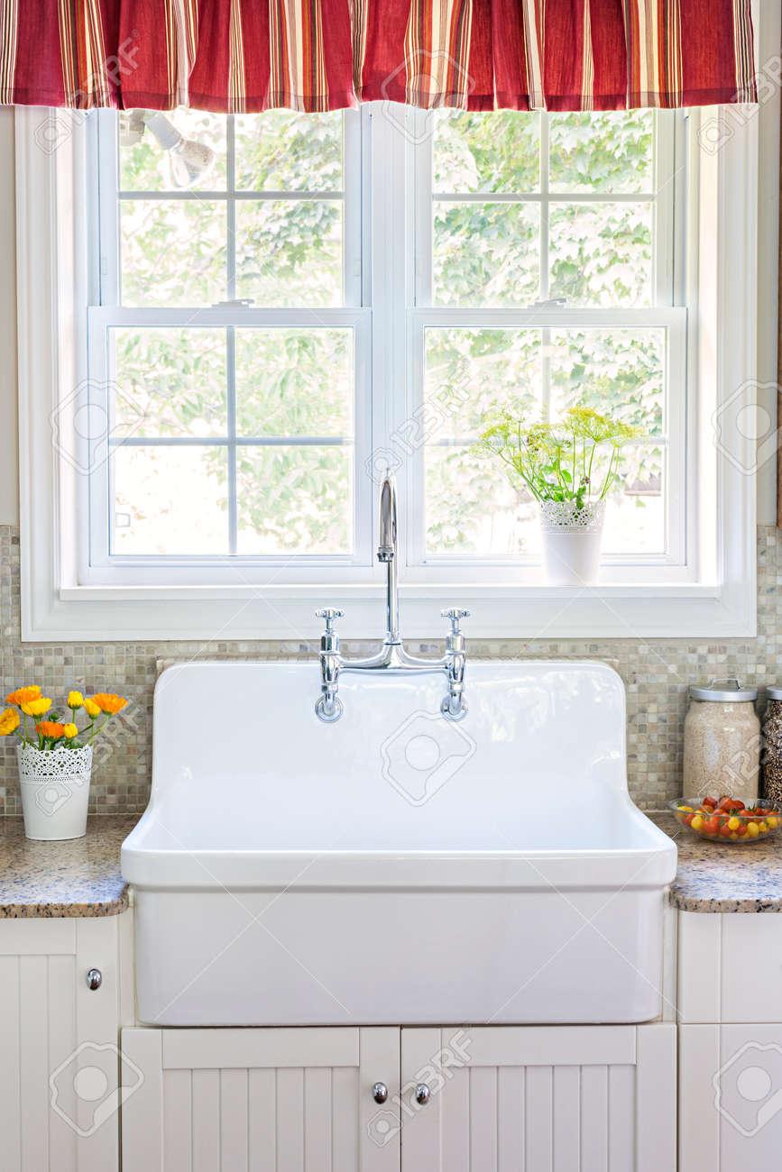 Kök inredning med stora rustika vitt porslin handfat och granit ...