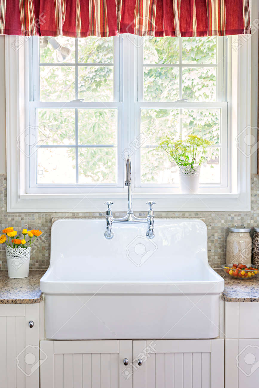 Kitchen interior with large rustic white porcelain sink and granite stone countertop under sunny window Stock Photo - 35893318