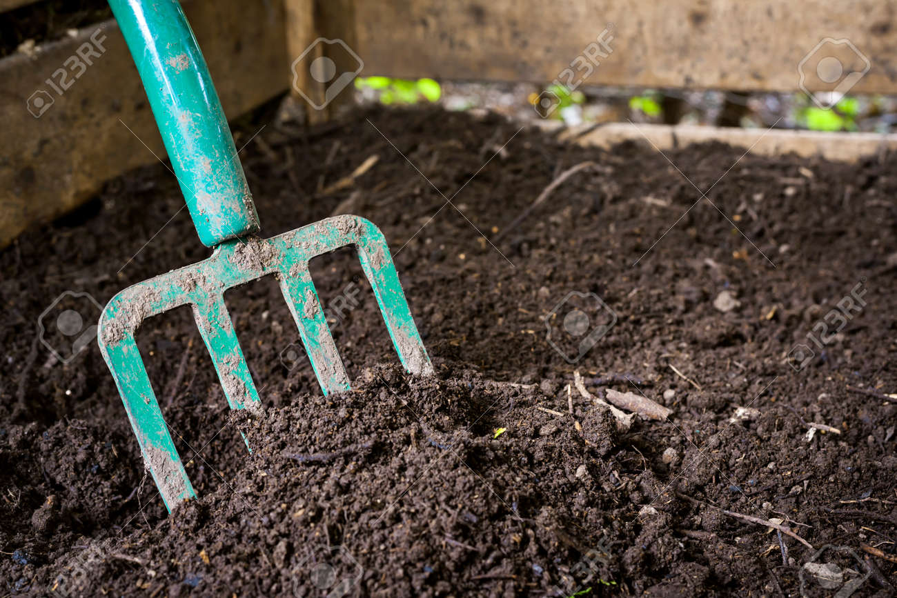Garden fork turning black composted soil in wooden compost bin Stock Photo - 36111264
