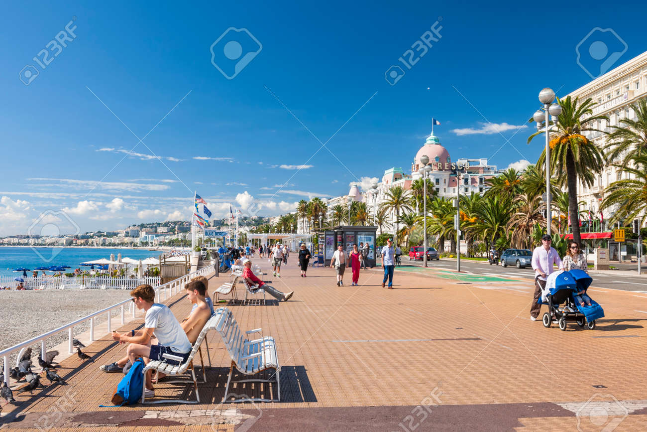 NICE, FRANCE - OCTOBER 2, 2014: People enjoying sunny weather and view of Mediterranean sea at English promenade (Promenade des Anglais), a great place for walking, jogging, biking or simply relaxing. - 37990291