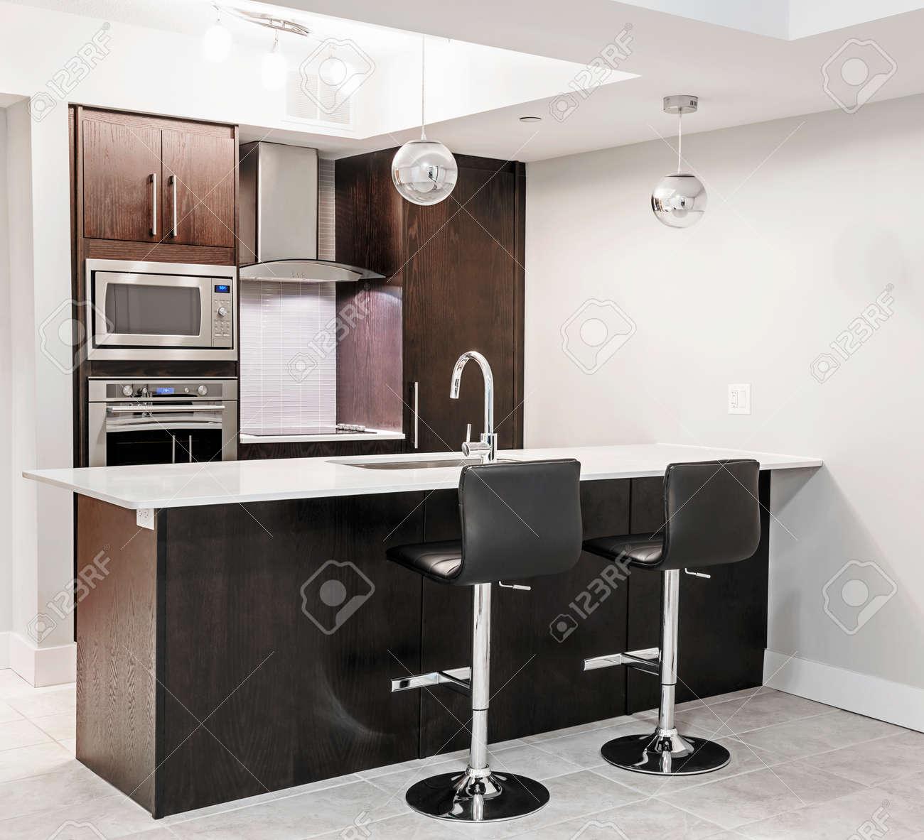 Modern luxury kitchen interior with dark wood cabinets, island..