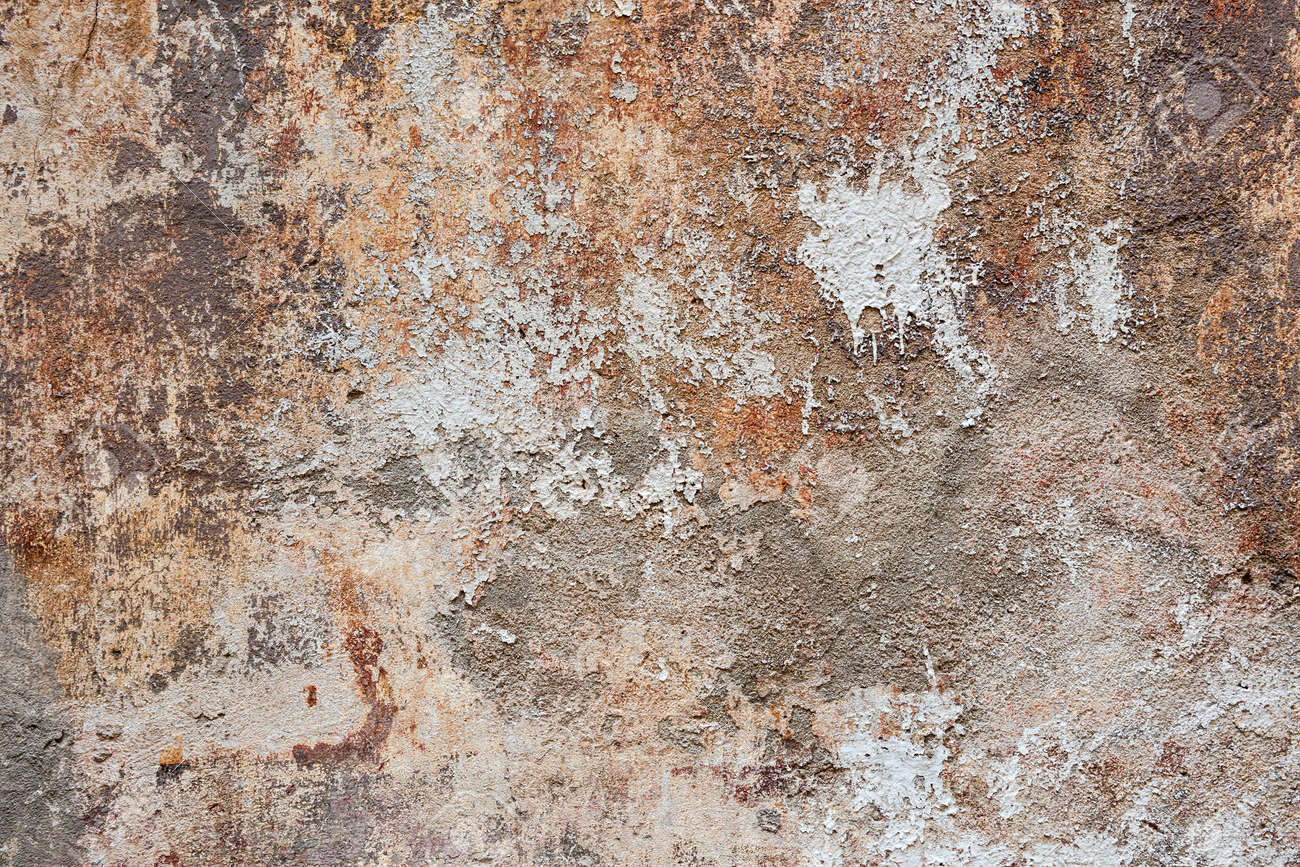 Abstract background of old painted plastered wall with peeling paint texture in brown, grey, and orange colors - 43832358