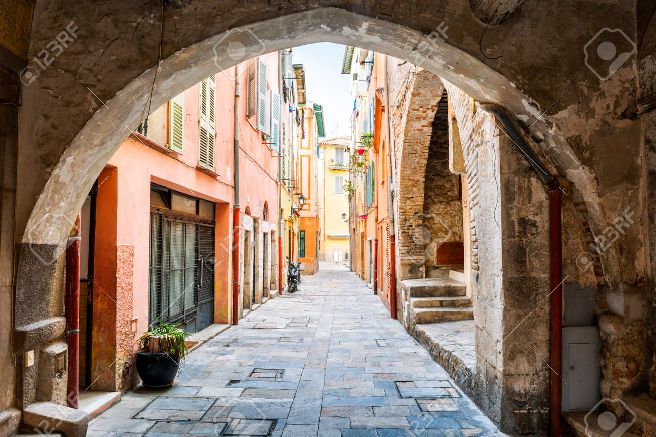 Narrow cobblestone street with colorful buildings viewed though stone arch in medieval town Villefranche-sur-Mer on French Riviera, France. Stock Photo - 44060189