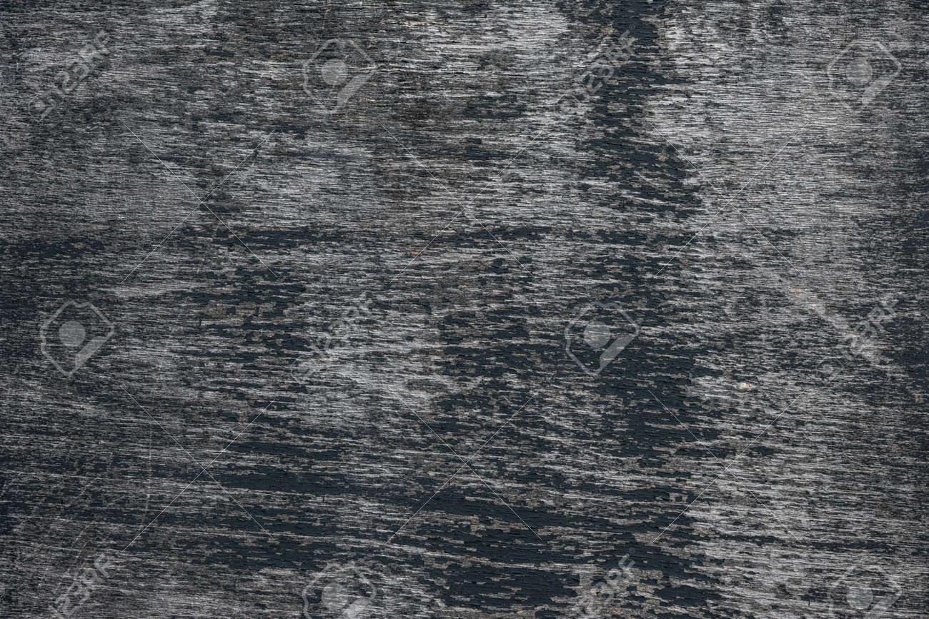 Background Of Dark Weathered Wood Texture With Peeling Black Paint Showing Grey Woodgrain Stock Photo