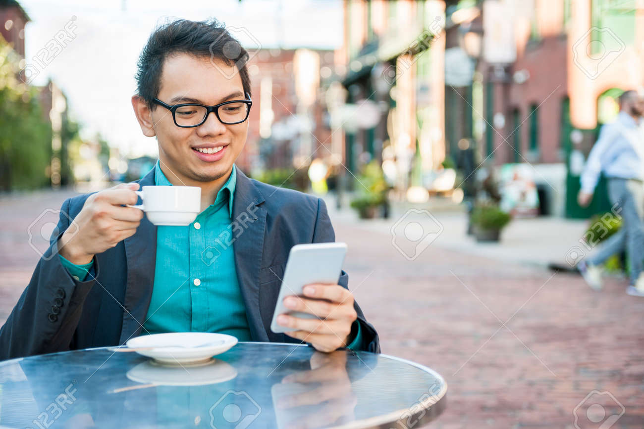 Young asian man in business casual attire sitting and smiling in relaxing outdoor cafe drinking cup of coffee while using mobile phone - 55759726