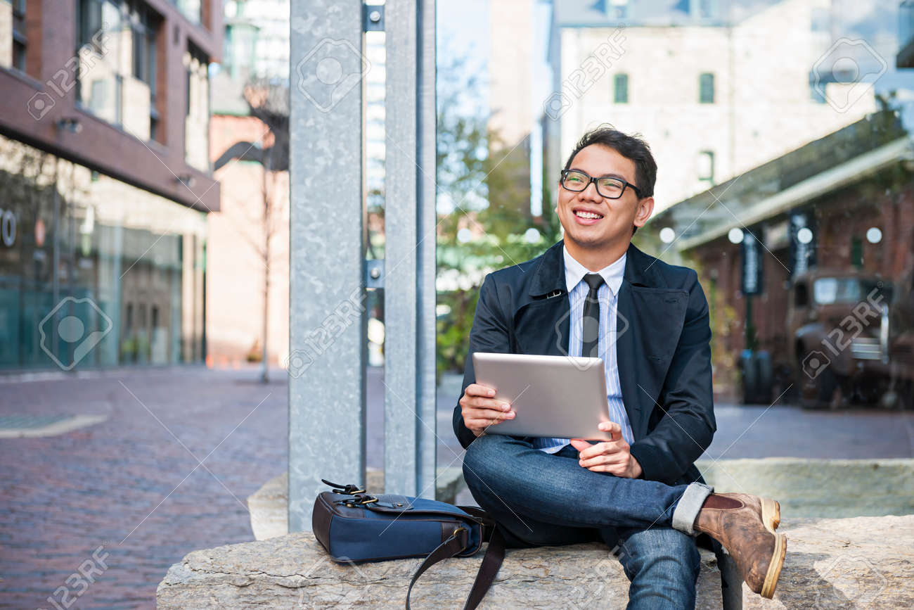 Young smiling asian business man holding a digital tablet sitting outside on city street looking away Stock Photo - 58163849