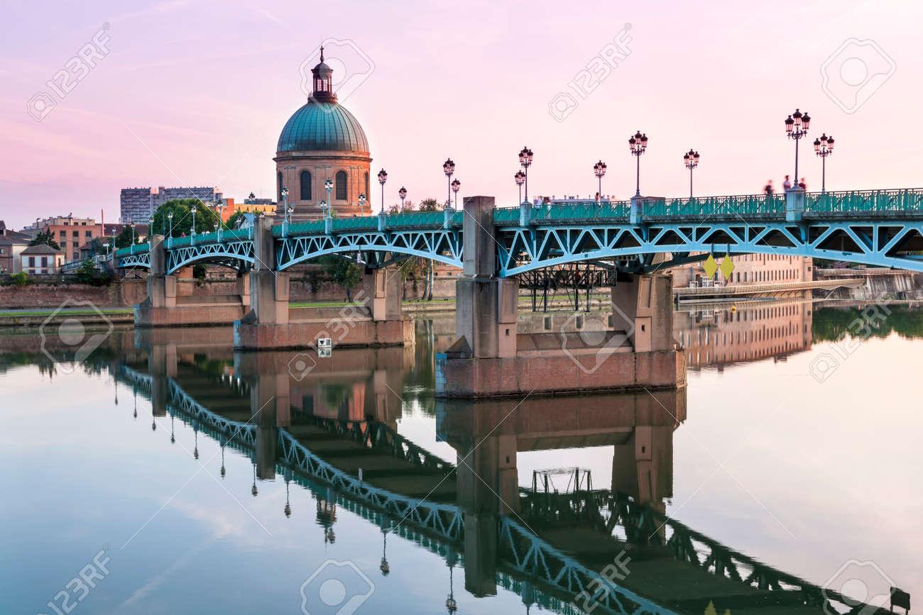 Saint-Pierre Bridge reflecting in Garonne river and Dome de la Grave at sunset in Toulouse, France - 64982495