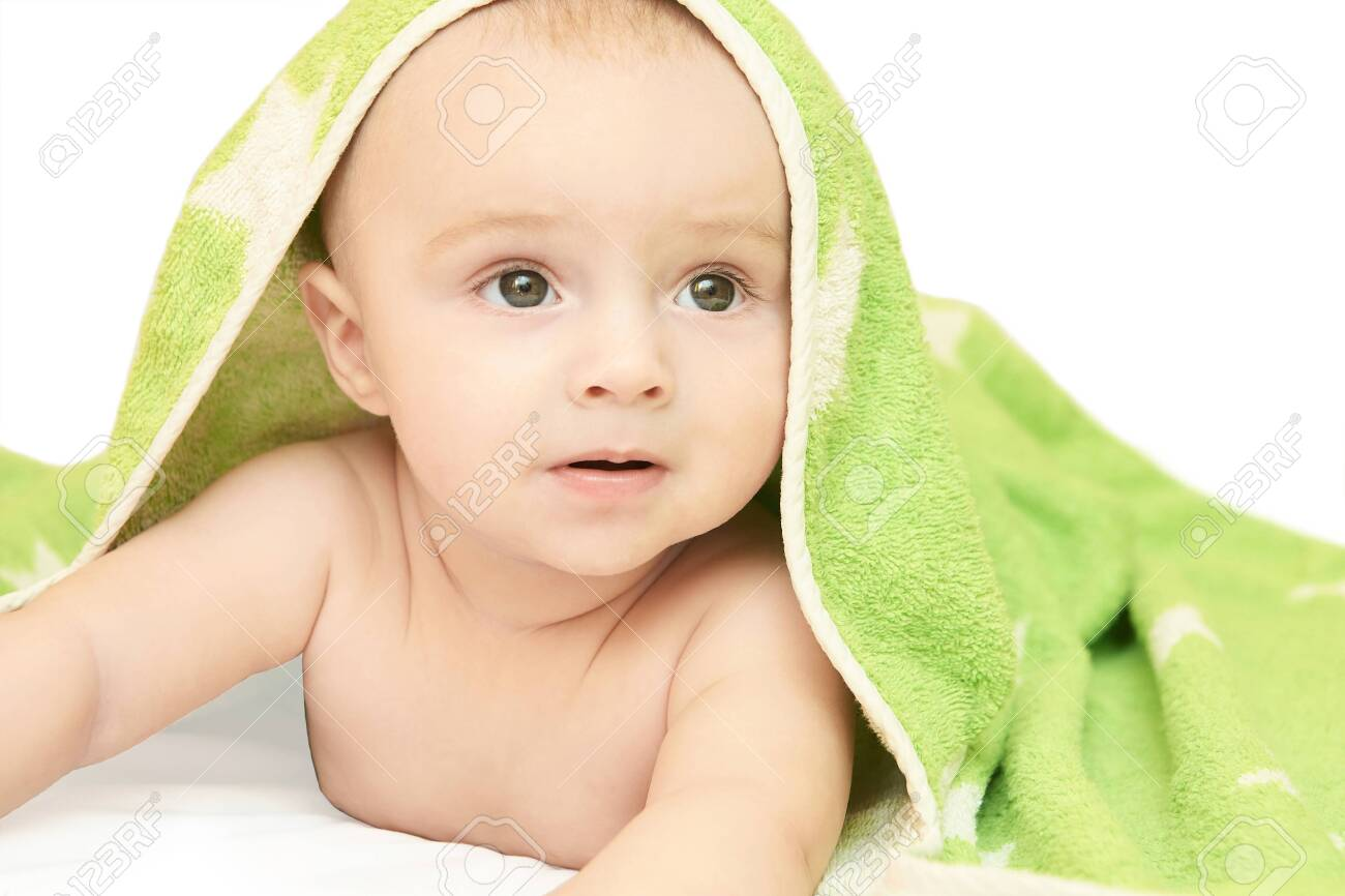 Cute little baby. Under bath towel. Happy kid portrait. White background. Lying at home bed. Infant playing. Beautiful bear. New human. Face skin care. Good emotion. Look side. - 152514739