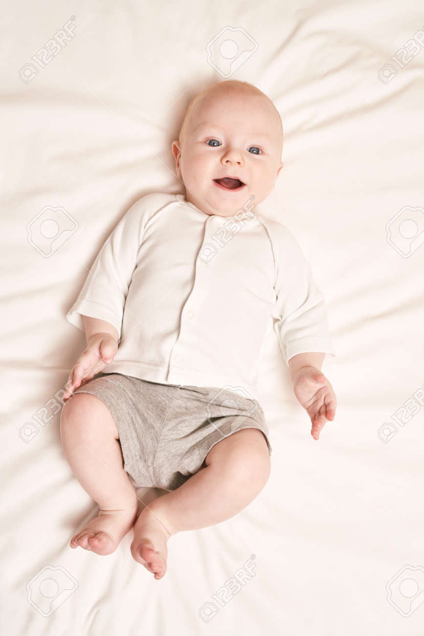 Cute small boy lying at bed. Childhood concept. Light background. Smiling child. Happy emotion. Copyspace. Stay home. Mockup. Children clothes - 168268139