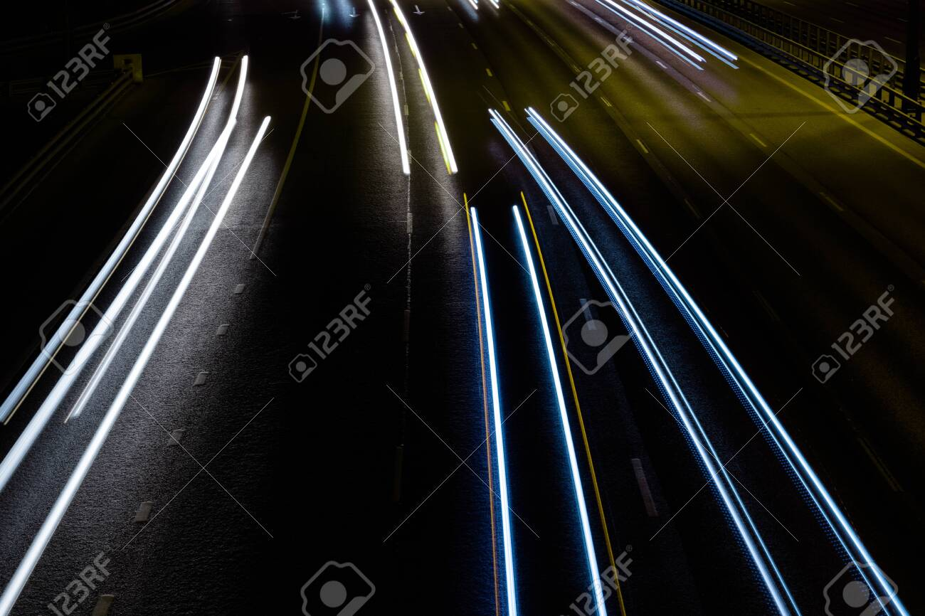 White and blue lights of a car in motion at long exposure on a night highway. Background with stripes. - 144201290