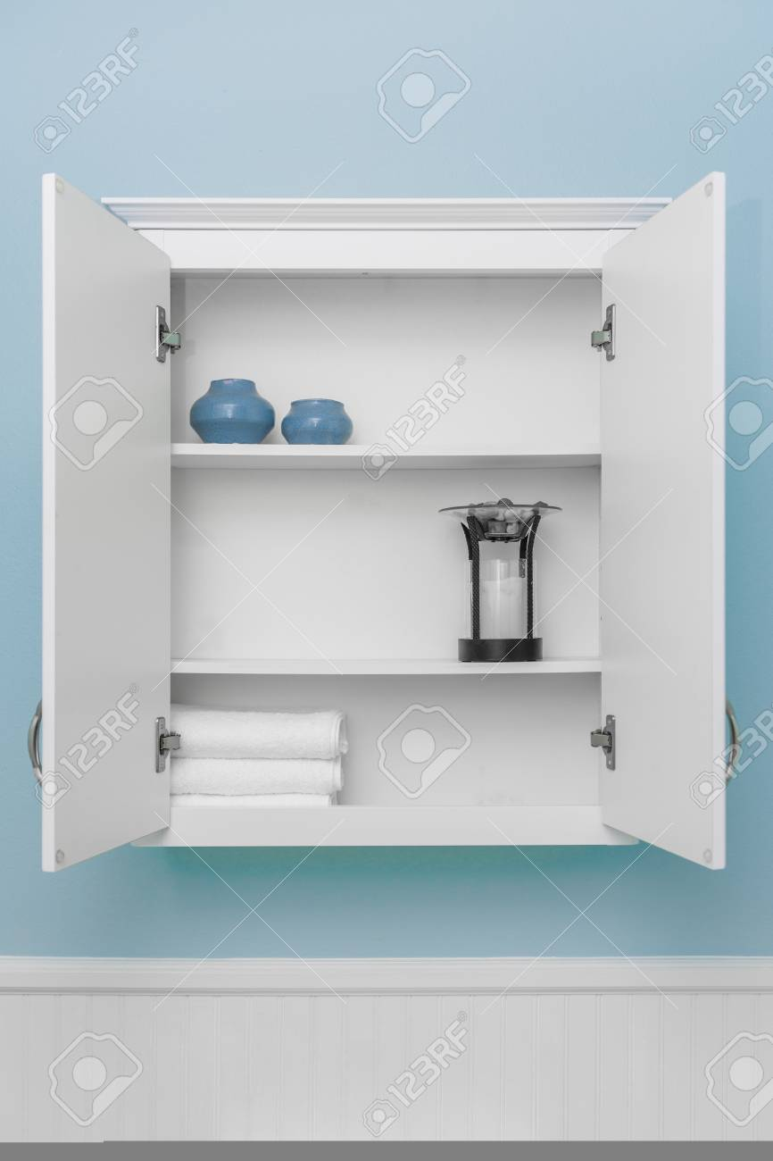 Stylish home decor on shelves of clean white cabinet, empty space for product display, light blue wall paint, white beadboard or wainscoting - 104247009