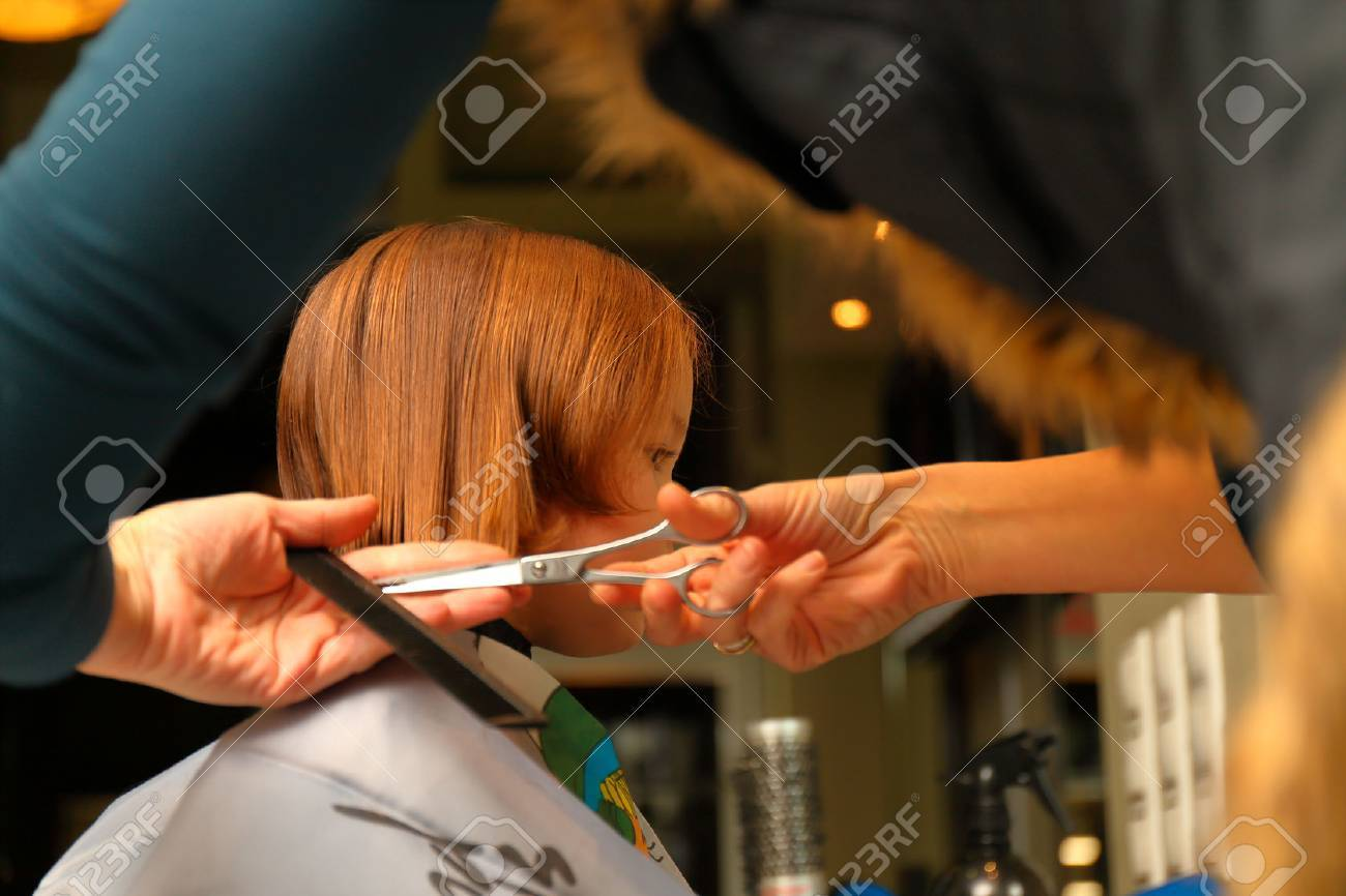 First Haircut Of Little Girl In Professional Hair Salon Stock Photo