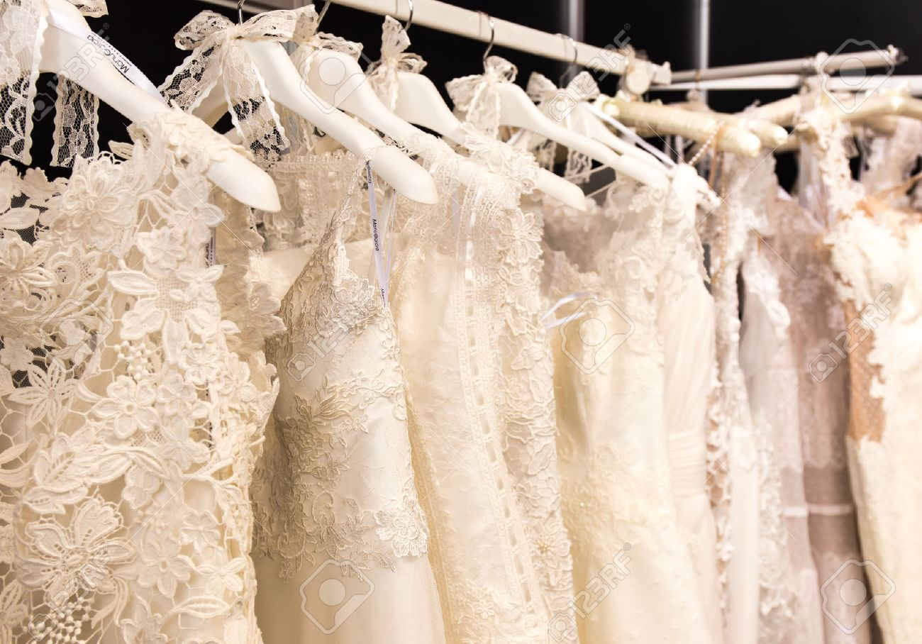 white wedding dresses hanging on shoulders and pegs - 54716165