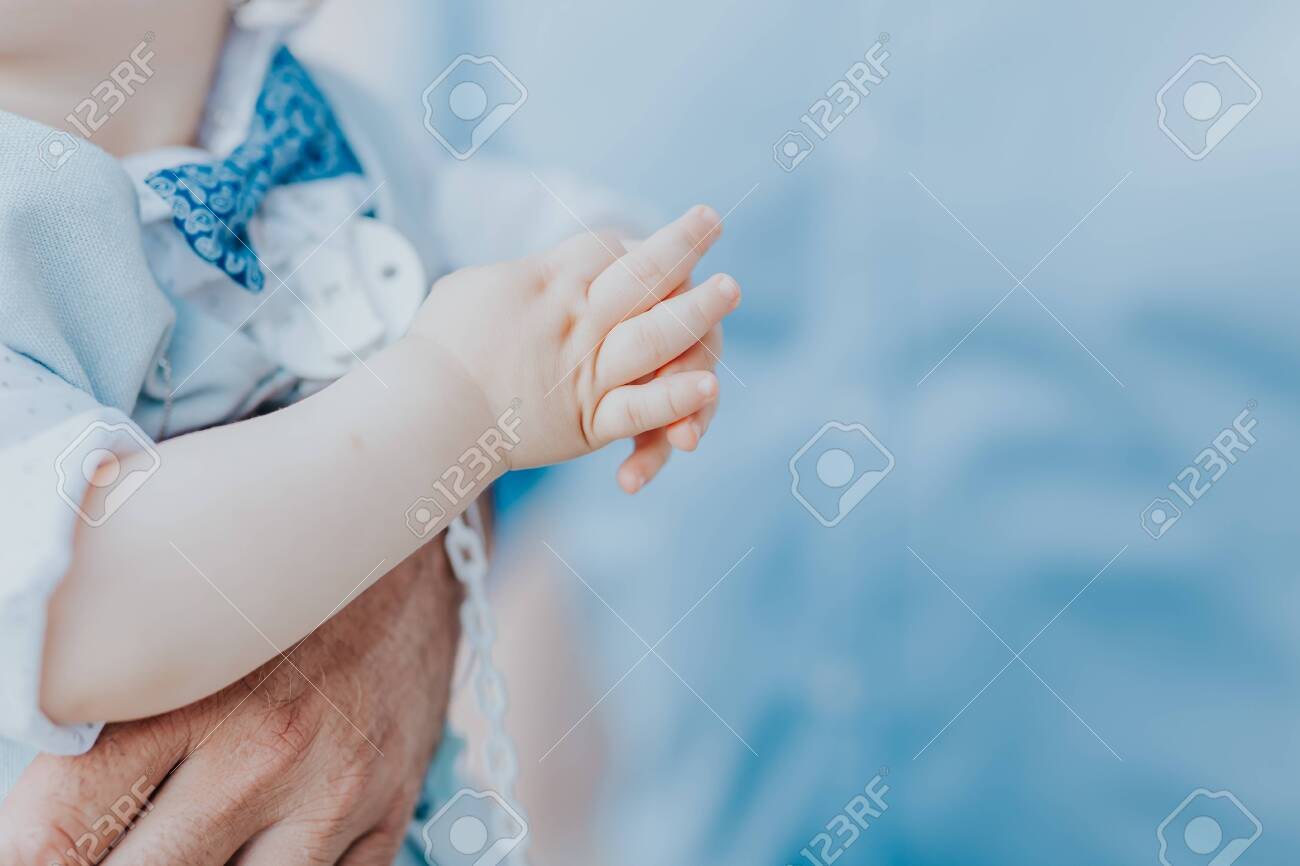 dad holds his son in his arms, a boy in a blue suit - 153446594