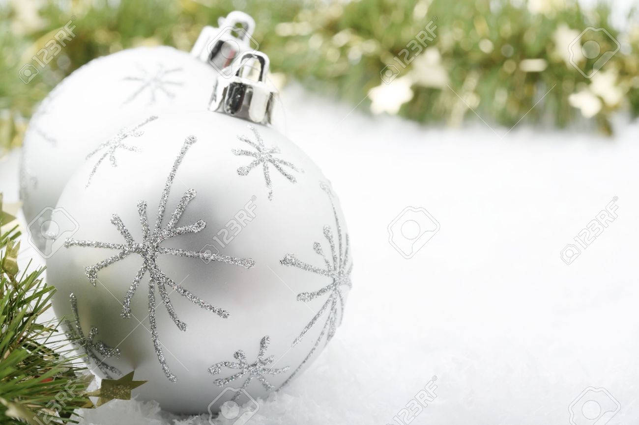 Un Gros Plan De Deux Boules D Argent De Noël De Couleur De Dessins D étoiles à Côté D Une Décoration De Guirlande Verte Reposant Sur Des Flocons De
