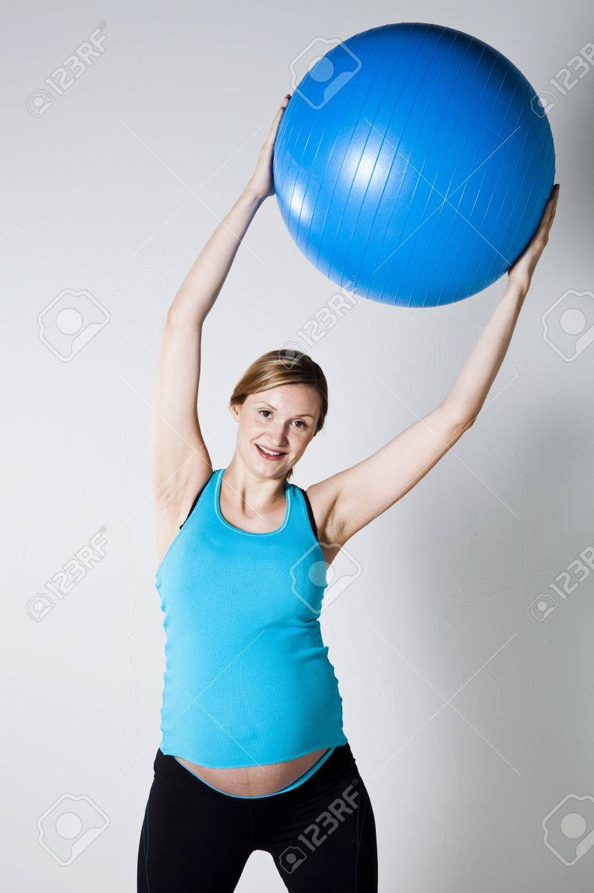 Pregnant woman exercising with a blue fitness ball held above head Stock Photo - 12970254