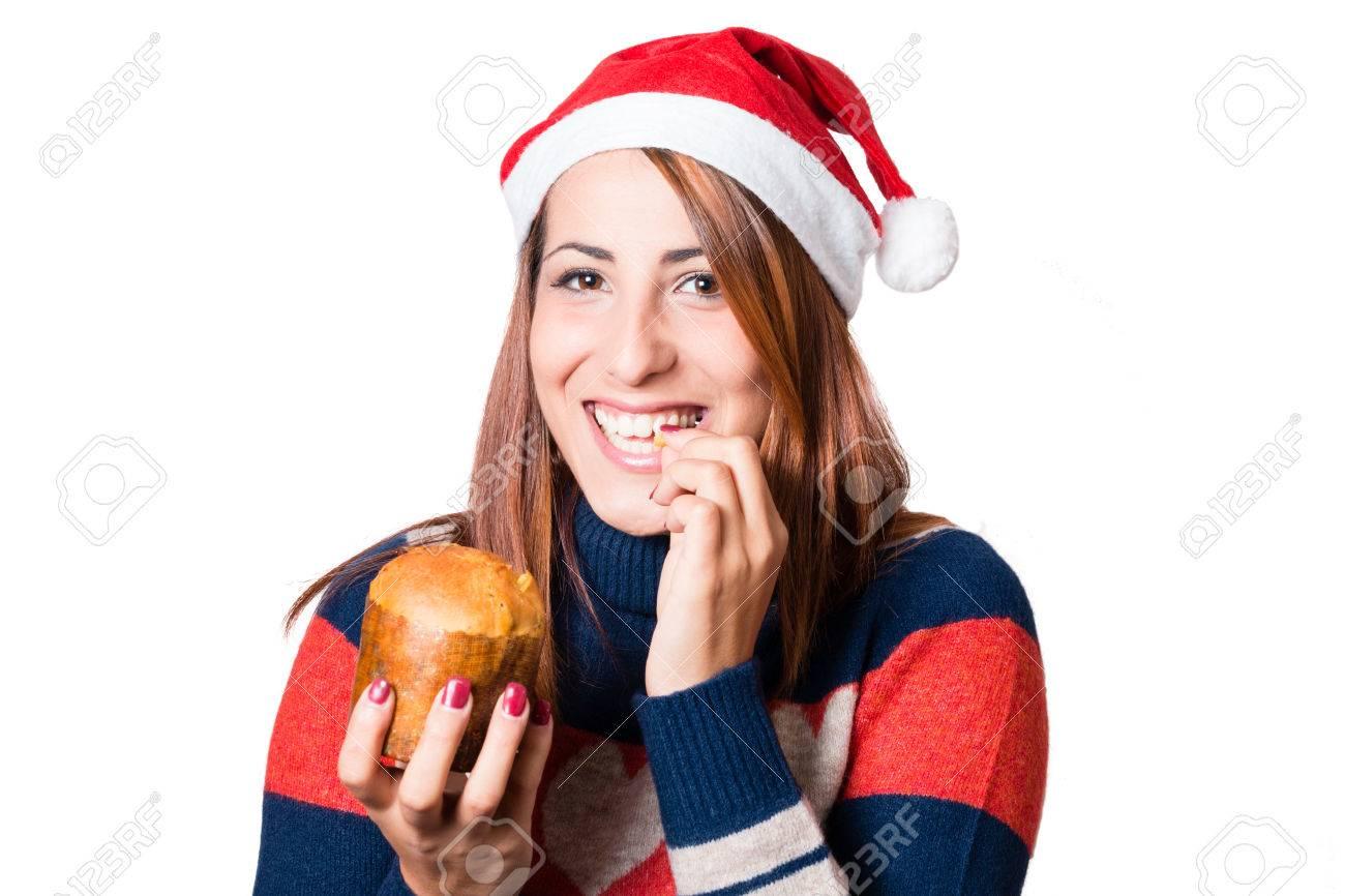 Foto de archivo - Hermosa mujer joven con sombrero de Papá Noel degustar un  pastel de Navidad típico italiano  Panettone. Sonreír 19084b29d35