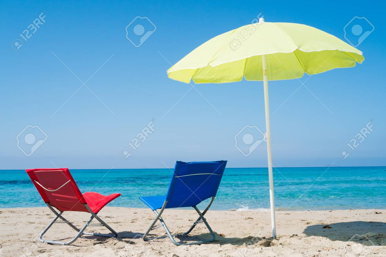 Stock Photo   Yellow Beach Umbrella And Two Lounge Chairs On A Beach In  Sardinia