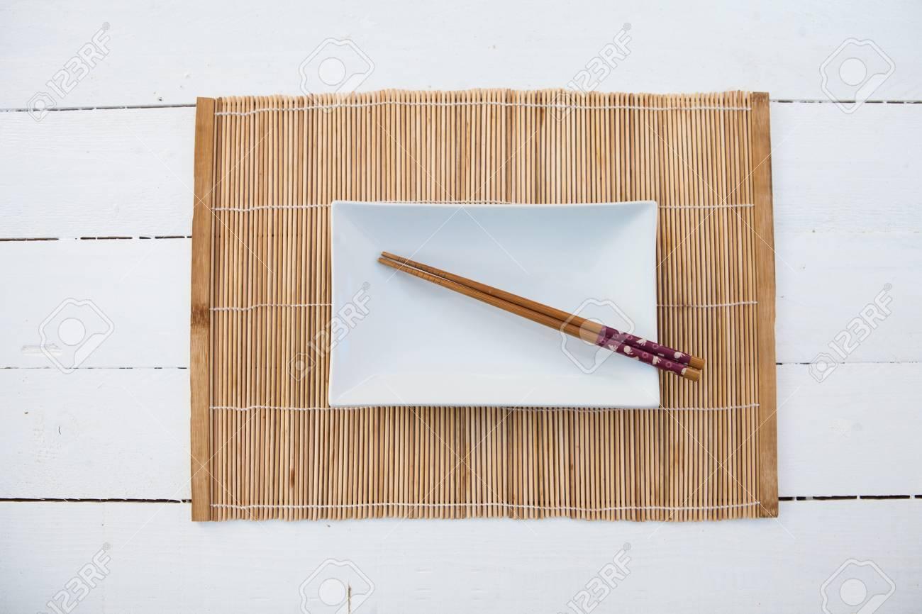 Copertura In Legno Bianco : Bianco quadrato piatto con le bacchette e una copertura di tabella