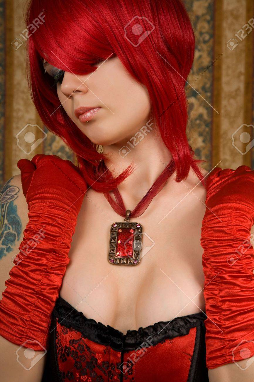 Attractive redhead woman in red corset, glamour background Stock Photo - 7052736