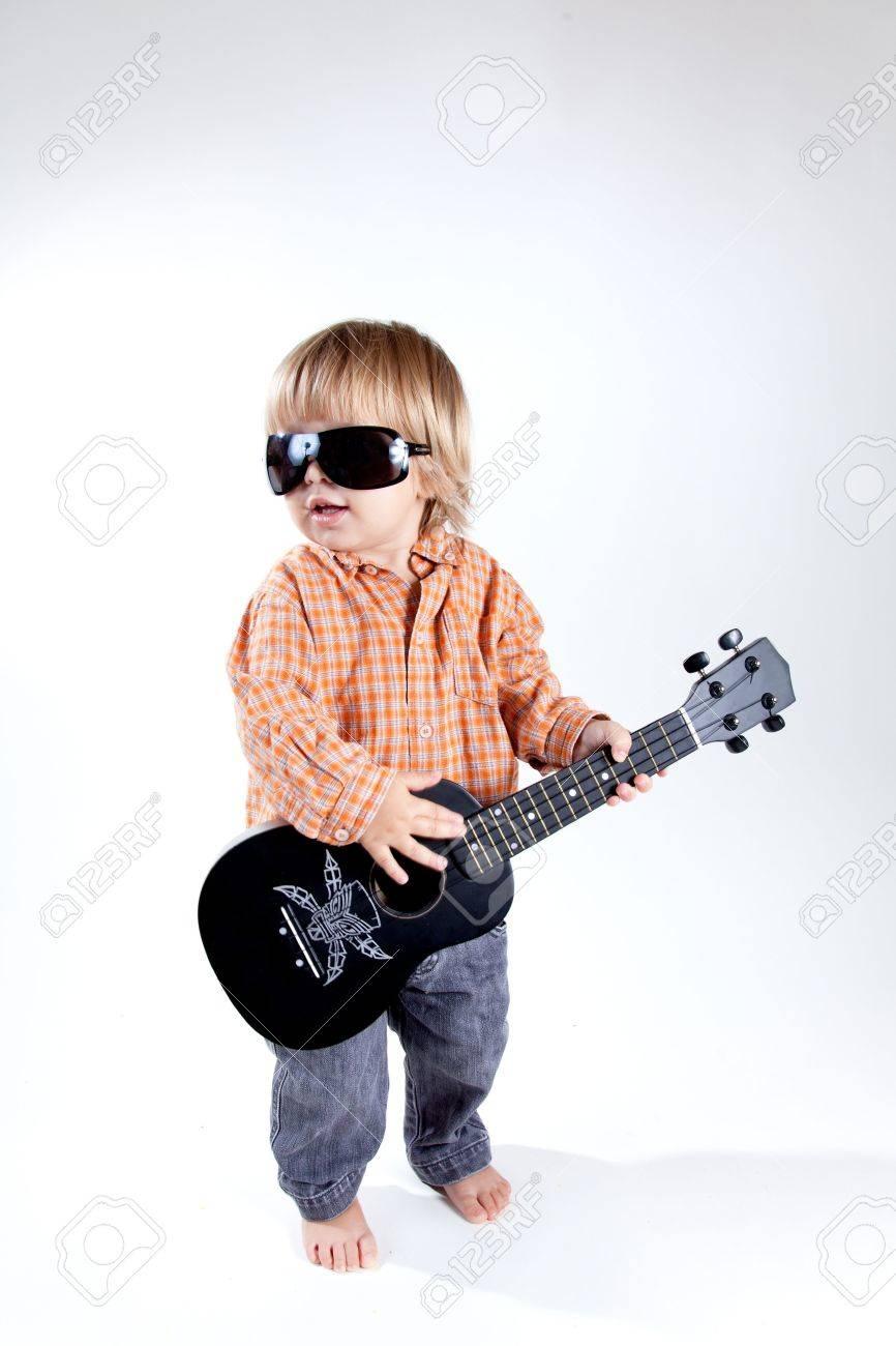 Funny little boy with ukulele guitar, studio shot Stock Photo - 7967874