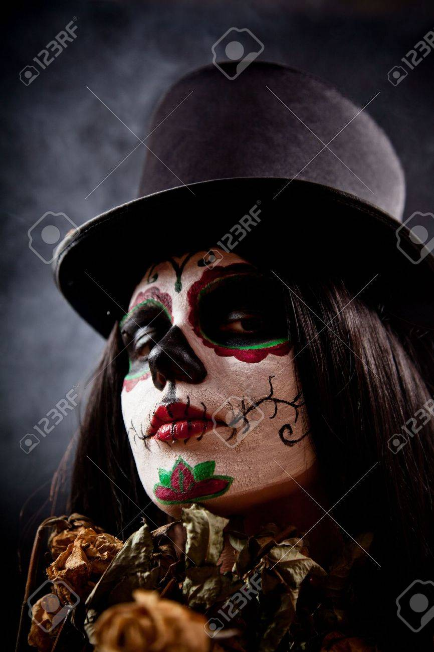 Sugar skull girl in tophat holding dead roses, studio shot Stock Photo - 8090752