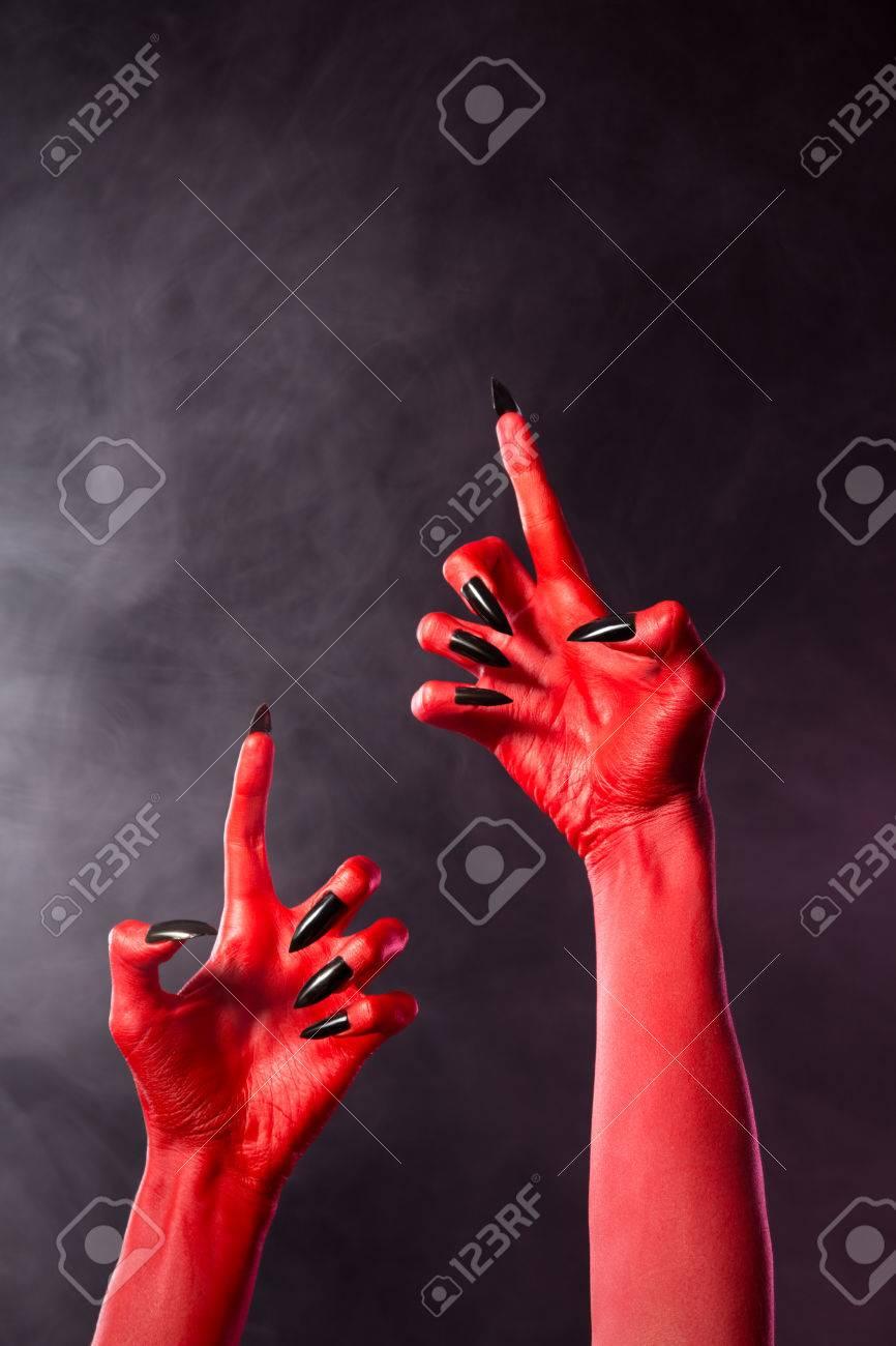 Banque d\u0027images , Creepy mains de diable rouge avec des ongles noirs, thème  Halloween