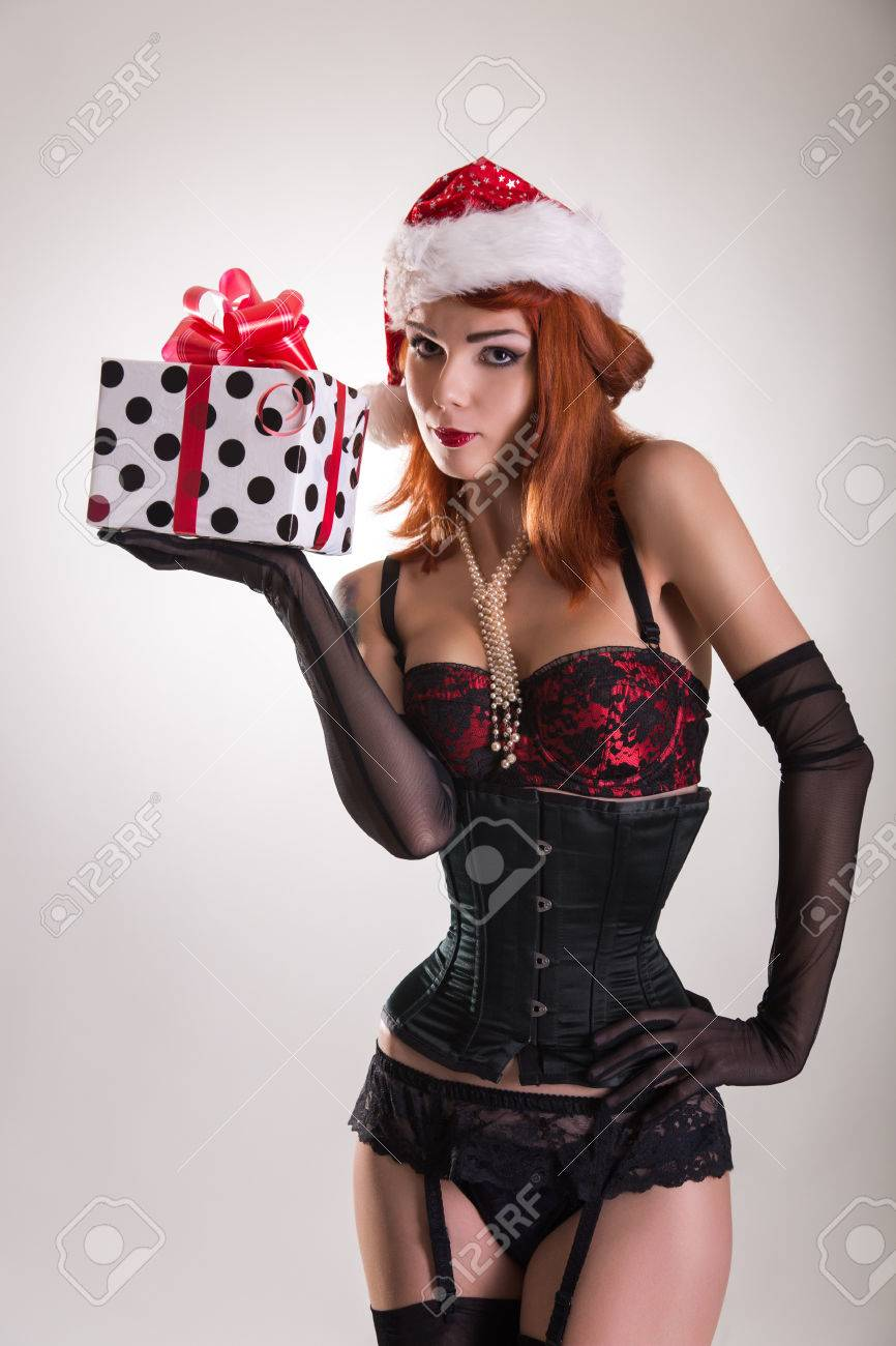 Pretty girl wearing pinup outfit and Santa Claus hat, holding gift box, Christmas theme Stock Photo - 23571166