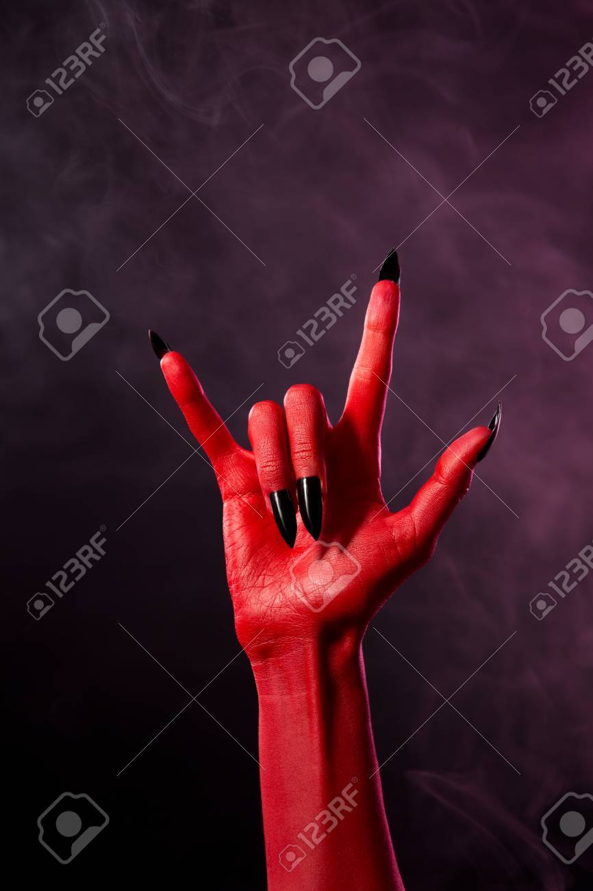 red devil hand with black sharp nails studio shot on smoky