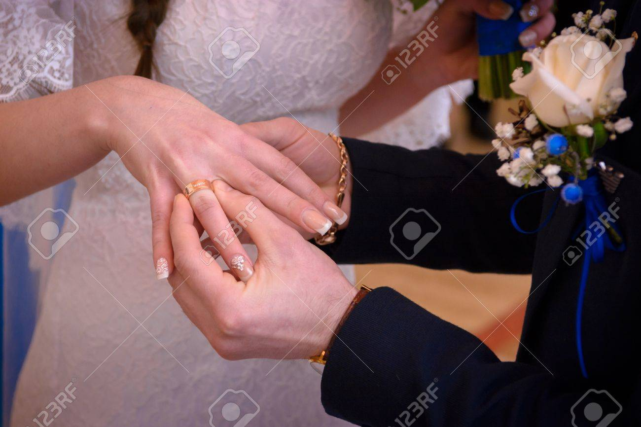 Newlyweds Exchange Rings, Groom Puts The Ring On The Bride\'s.. Stock ...