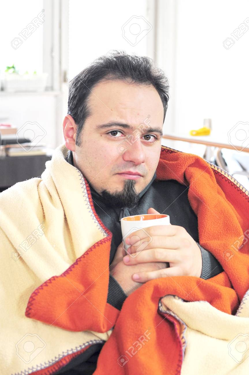 Young man in blanket holding cup of tea Stock Photo - 16660962
