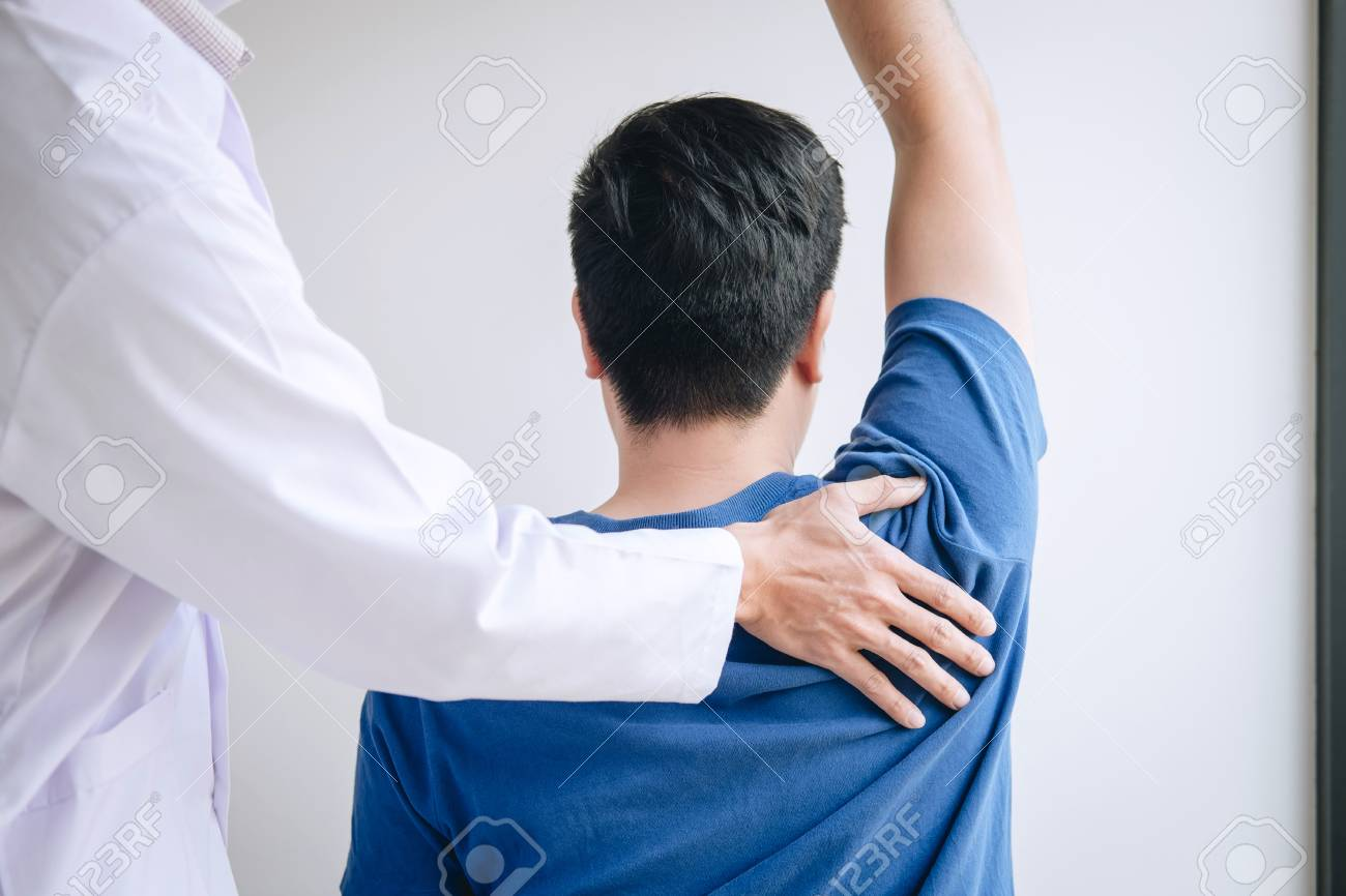 Doctor physiotherapist assisting a male patient while giving exercising treatment massaging the shoulder of patient in a physio room, rehabilitation physiotherapy concept. - 120403437