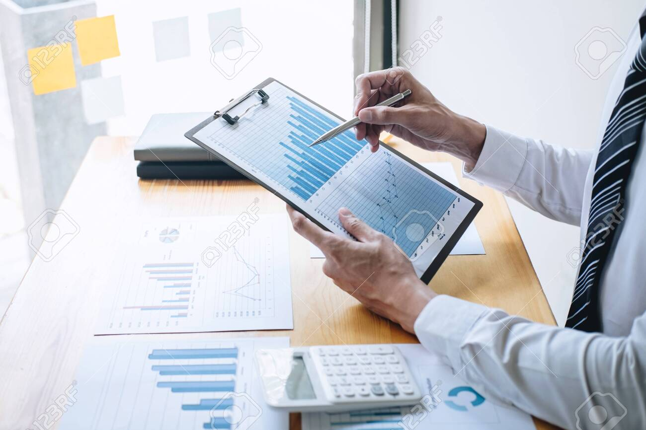 Businessman accountant working analyzing and calculating expense financial annual financial report balance sheet statement and analyze document graph and diagram, doing finance making notes on report. - 126102425