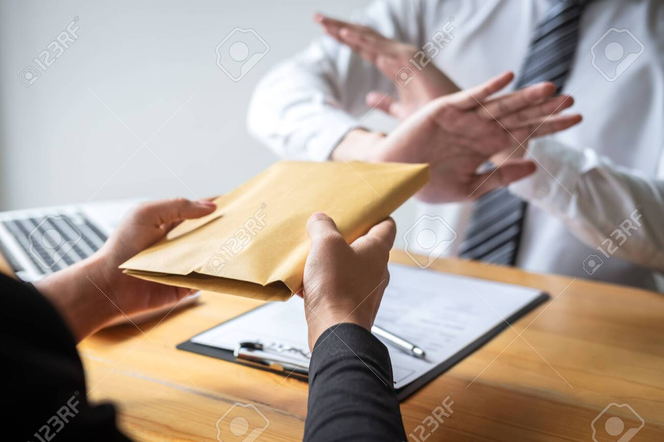 Anti bribery and corruption concept, Business man refusing and don't receive money banknote in envelope offer from business people to accept agreement contract of investment deal. - 126104310