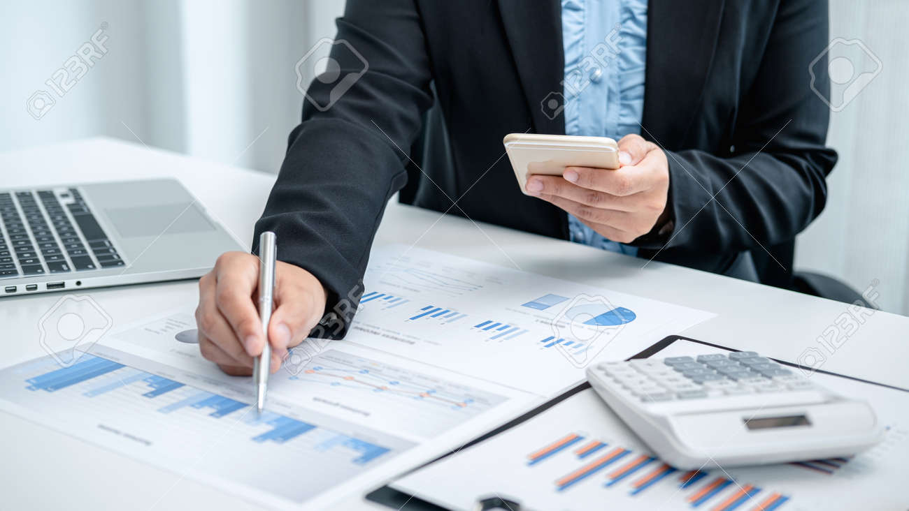 Business woman hold pen and phone use to record investment data, to check cost and profit used for doing business - 165277228