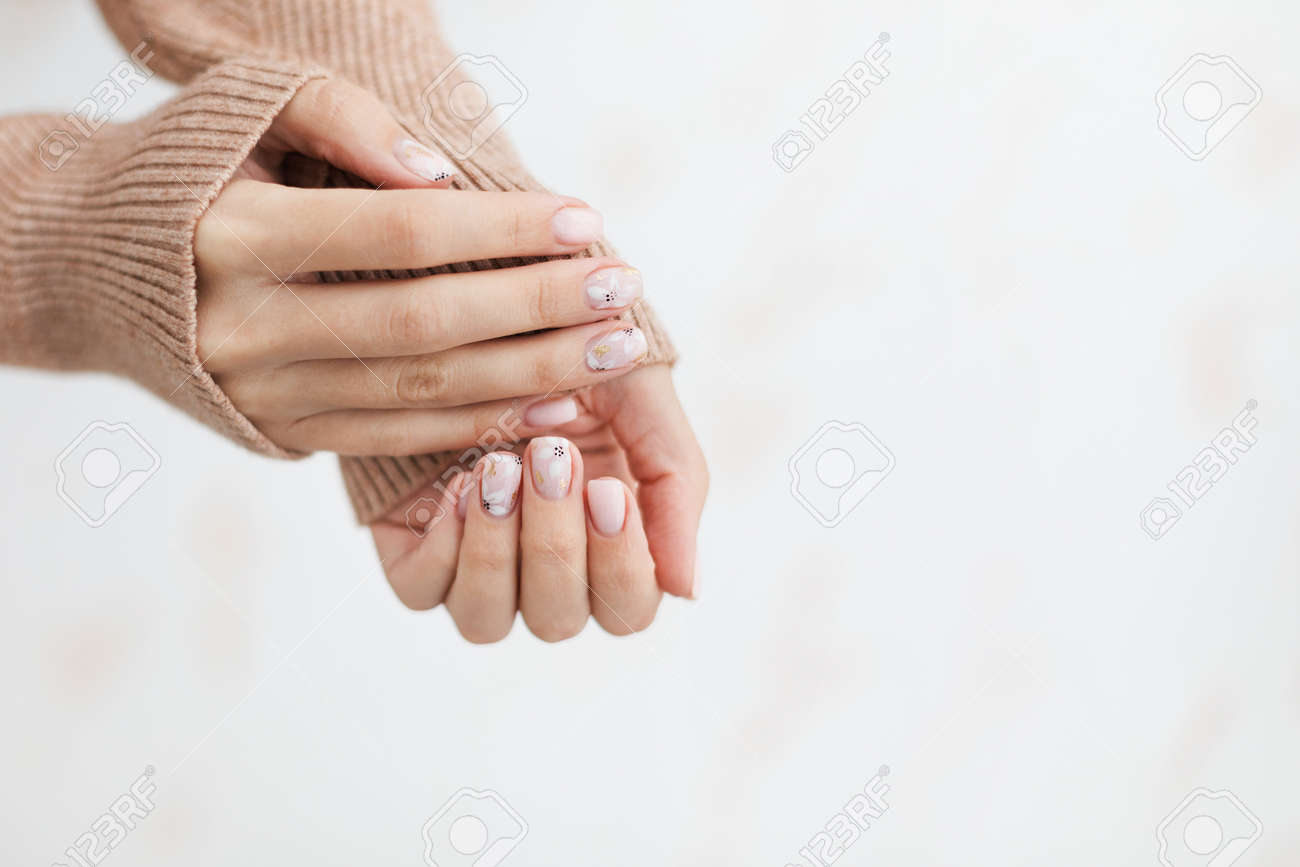 Female hand manicure close up view with warm sweater on light background. - 163588272