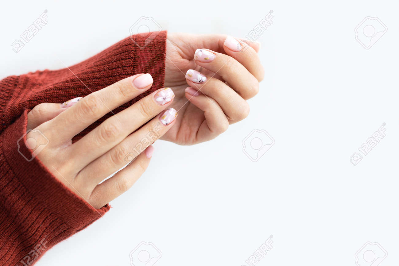 Female hand manicure close up view with warm sweater on light background. - 163588322